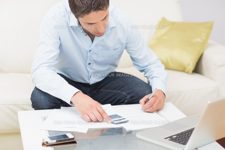 Young man with bills calculator and laptop at homeの写真素材 [FYI00485683]
