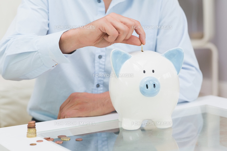 Mid section of a man putting some coins into a piggy bankの写真素材 [FYI00485684]