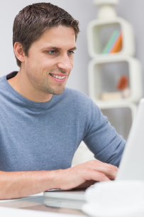 Smiling young man using laptop in living roomの写真素材 [FYI00485685]