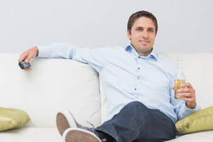 Relaxed man with a drink and remote control sitting on sofa at homeの写真素材 [FYI00485686]