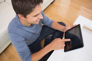 Overhead view of man using digital tablet in living roomの写真素材 [FYI00485687]