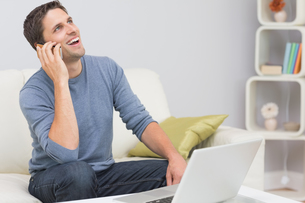 Cheerful man using cellphone and laptop in living roomの写真素材 [FYI00485688]