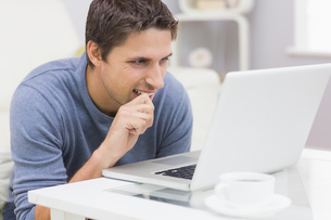 Thoughtful young man using laptop in living roomの写真素材 [FYI00485690]