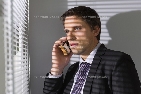 Businessman peeking through blinds while on call in officeの写真素材 [FYI00485691]