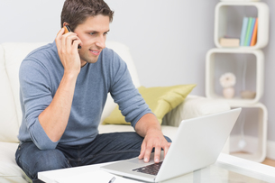 Smiling man using cellphone and laptop in living roomの写真素材 [FYI00485692]