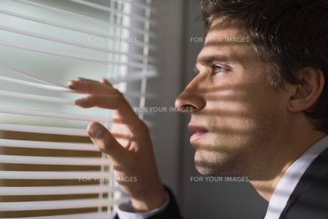 Serious businessman peeking through blinds in officeの写真素材 [FYI00485694]