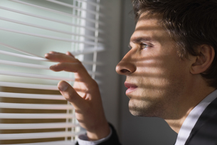 Serious businessman peeking through blinds in officeの写真素材 [FYI00485694]