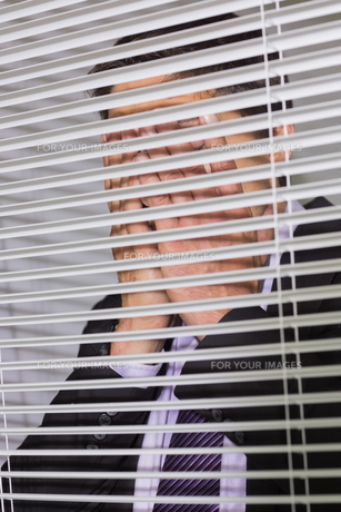Businessman with head in hands in front of blinds in officeの写真素材 [FYI00485697]