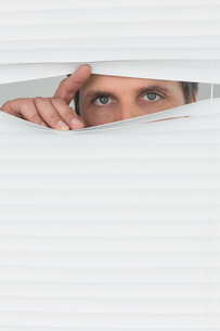 Green eyed businessman peeking through blindsの写真素材 [FYI00485698]