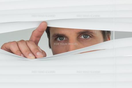 Closeup of green eyed businessman peeking through blindsの素材 [FYI00485699]