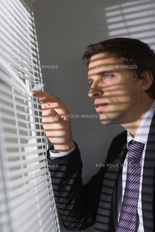 Serious young businessman peeking through blinds in officeの素材 [FYI00485700]