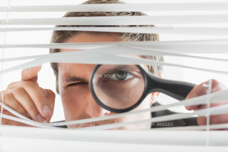 Businessman peeking through blinds with magnifying glassの素材 [FYI00485701]