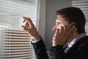 Businessman peeking through blinds while on call in officeの写真素材 [FYI00485703]
