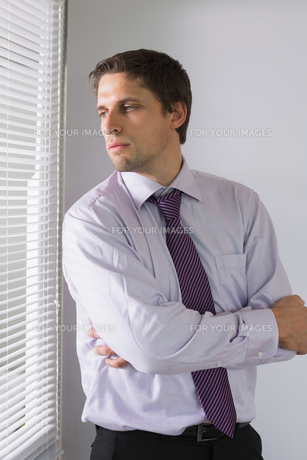 Serious businessman peeking through blinds in officeの写真素材 [FYI00485704]