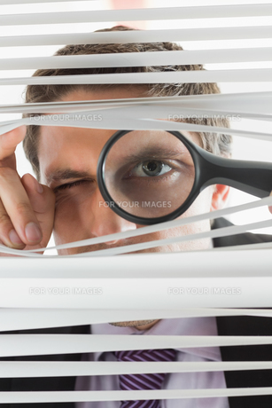 Businessman peeking through blinds with magnifying glassの素材 [FYI00485705]