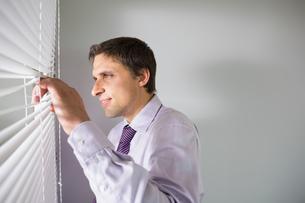 Businessman peeking through blinds in officeの写真素材 [FYI00485706]