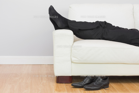 Low section of businessman resting on sofa in living roomの写真素材 [FYI00485707]