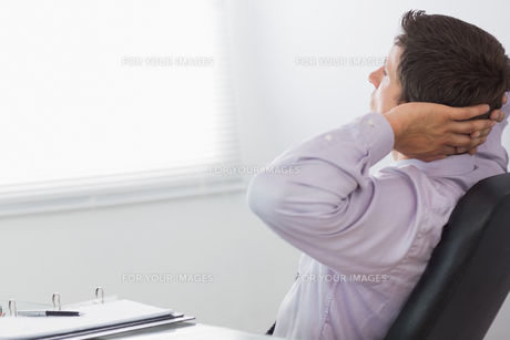 Thoughtful relaxed businessman sitting in officeの写真素材 [FYI00485709]