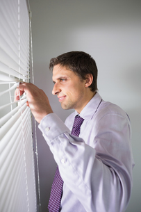Young businessman peeking through blinds in officeの写真素材 [FYI00485710]