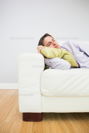 Tired businessman sleeping on sofa in living roomの素材 [FYI00485711]