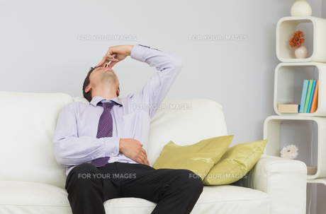 Tired businessman sitting on sofa in living roomの写真素材 [FYI00485712]