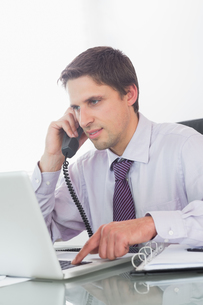 Businessman using telephone and laptop at deskの写真素材 [FYI00485713]
