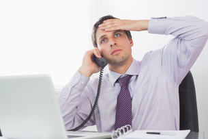 Worried businessman on call at deskの写真素材 [FYI00485714]