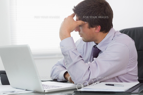 Worried businessman with laptop sitting in officeの素材 [FYI00485716]