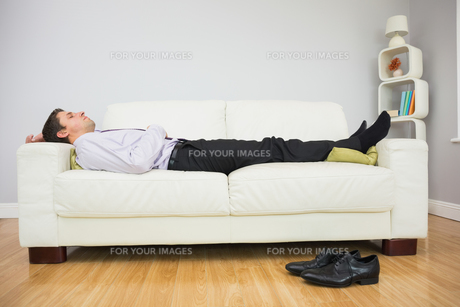Tired businessman sleeping on sofa in living roomの写真素材 [FYI00485717]