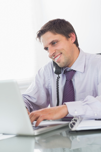 Businessman using telephone and laptop at deskの写真素材 [FYI00485718]