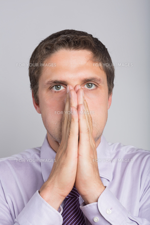 Green eyed businessman with hands covering faceの写真素材 [FYI00485720]