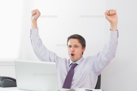 Businessman cheering in front of laptop in officeの写真素材 [FYI00485722]