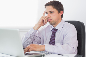 Worried businessman using laptop in officeの写真素材 [FYI00485723]