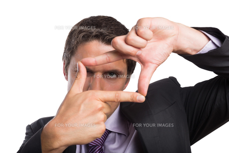 Closeup of a businessman looking through finger frameの素材 [FYI00485727]