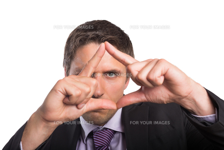 Closeup of businessman looking through finger frameの素材 [FYI00485728]