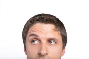 Closeup of a green eyed man raising eyebrowの写真素材 [FYI00485729]