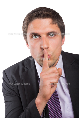 Green eyed businessman with finger to his lipsの写真素材 [FYI00485734]