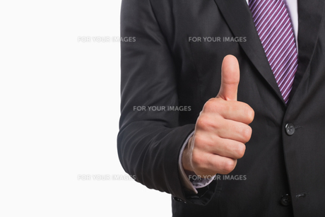 Mid section of a businessman gesturing thumbs upの素材 [FYI00485736]