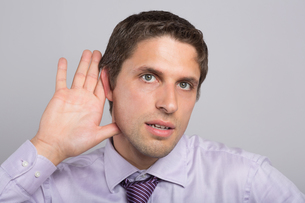 Closeup of a green eyed businessman with hand to earの写真素材 [FYI00485738]