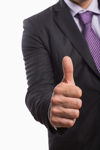 Mid section of a businessman gesturing thumbs upの写真素材 [FYI00485740]