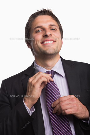 Portrait of a happy businessman adjusting tieの写真素材 [FYI00485741]