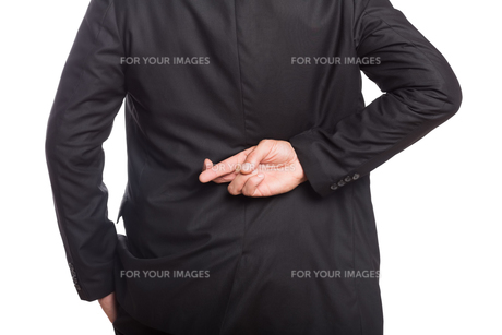 Mid section of a businessman with crossed fingersの写真素材 [FYI00485751]