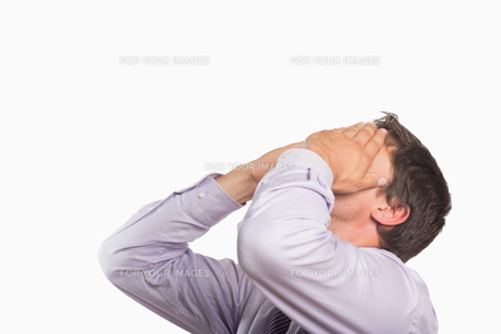 Worried businessman with hands covering faceの素材 [FYI00485754]