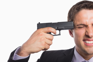 Closeup of a businessman holding a gun to headの写真素材 [FYI00485756]