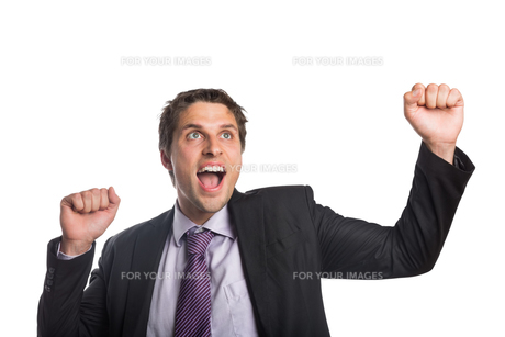 Cheerful businessman cheering as he looks upの写真素材 [FYI00485757]