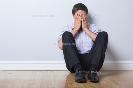 Businessman sitting on floor with hands covering face in empty roomの写真素材 [FYI00485764]