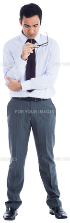 Unsmiling businessman holding glassesの素材 [FYI00485797]