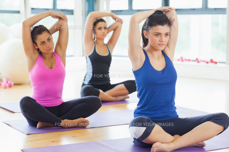 Class stretching hands behind heads on mats at yoga classの素材 [FYI00485825]