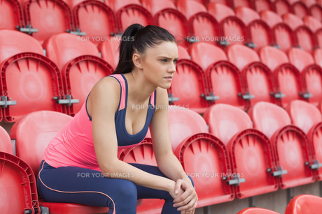 Serious toned young woman sitting on chair in the stadiumの写真素材 [FYI00485826]