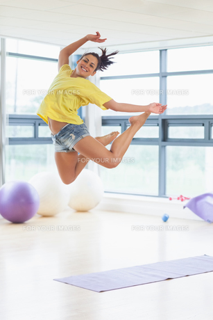 Young woman jumping in fitness studioの写真素材 [FYI00485827]